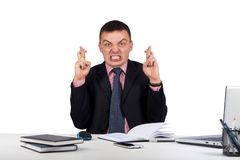 Επιθυμώντας τον επιχειρηματία που διασχίζει τα δάχτυλά του στο γραφείο του που απομονώνεται στο άσπρο υπόβαθρο στοκ φωτογραφίες
