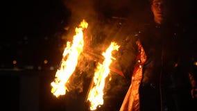 Επικίνδυνη απόδοση πυρκαγιάς στην οδό, ένα άτομο στο κοστούμι που κρατά μια καίγοντας καρέκλα απόθεμα βίντεο
