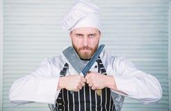 Επικίνδυνη κουζίνα αρχιμάγειρας έτοιμος για το μαγείρεμα βέβαιο άτομο στο μαχαίρι λαβής ποδιών και καπέλων το γενειοφόρο άτομο αγ στοκ φωτογραφία με δικαίωμα ελεύθερης χρήσης