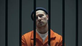 Επικίνδυνος αλαζονικός φυλακισμένος που στέκεται πίσω από τα κάγκελα και που παρουσιάζει δεμένα με χειροπέδες χέρια απόθεμα βίντεο