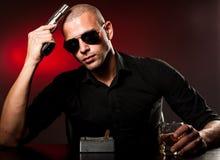 Επικίνδυνο άτομο με ένα πυροβόλο όπλο και τα γυαλιά ηλίου Στοκ εικόνα με δικαίωμα ελεύθερης χρήσης