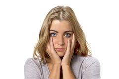 Επικεφαλής πορτρέτο του νέου όμορφου και γλυκού ξανθού κοριτσιού με τα μπλε μάτια που φαίνεται λυπημένου και καταθλιπτικού, ντροπ στοκ φωτογραφία