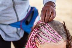 Επικεφαλής του μικρού κοριτσιού με τις λεπτές κοτσίδες γυναικών mades στο αφρικανικό ύφος, διαδικασία πλεξίματος στοκ εικόνες