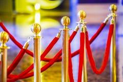Επικεφαλής χρυσό οδόφραγμα πόλων σφαιρών πολυτέλειας με το κόκκινο βελούδο στοκ εικόνες