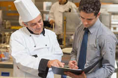 Επικεφαλής αρχιμάγειρας και σερβιτόρος που συζητούν τις επιλογές Στοκ Εικόνα