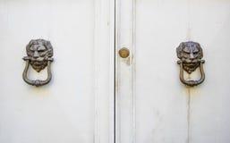 Επικεφαλής ρόπτρα λιονταριών σε μια παλαιά άσπρη ξύλινη πόρτα Στοκ Φωτογραφίες