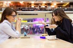 Επικοινωνία της ενήλικων μητέρας και του έφηβη Πίνακας υποβάθρου στον καφέ, στο ψωνίζοντας κέντρο ψυχαγωγίας λεωφόρων Στοκ Φωτογραφία