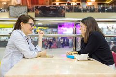 Επικοινωνία της ενήλικων μητέρας και του έφηβη Πίνακας υποβάθρου στον καφέ, στο ψωνίζοντας κέντρο ψυχαγωγίας λεωφόρων Στοκ Εικόνες