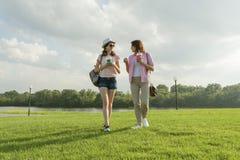 Επικοινωνία του γονέα και του εφήβου Η μητέρα μιλά στην κόρη εφήβων της για 14 έτη, που περπατά γύρω από το πάρκο στο ηλιόλουστο  στοκ φωτογραφία με δικαίωμα ελεύθερης χρήσης