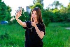 Επικοινωνεί στα κοινωνικά δίκτυα Το χέρι παρουσιάζει χειρονομία όπως, έγκριση Νέα γυναίκα brunette που χαμογελά ευτυχώς το καλοκα στοκ φωτογραφίες