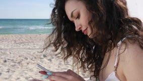 Επικοινωνώντας μέσω του κινητού τηλεφώνου στις θερινές διακοπές, το κορίτσι και το κοινωνικό δίκτυο ξεφυλλίσματος στη συσκευή, νέ απόθεμα βίντεο
