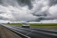Επικός ουρανός, γρήγορα κινούμενο αυτοκίνητο στο δρόμο στοκ εικόνες