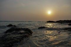 Επικό ηλιοβασίλεμα πέρα από την παραλία με τους βράχους και τη θάλασσα, τις διακοπές συγκίνησης και τον ταξιδιώτη τουρισμού διακο Στοκ φωτογραφίες με δικαίωμα ελεύθερης χρήσης