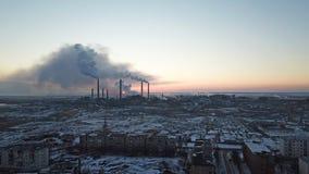 Επικό ηλιοβασίλεμα στο υπόβαθρο ενός καπνίζοντας εργοστασίου Ο κόκκινος ήλιος με τις φωτεινές ακτίνες υπερβαίνει τα εργοστάσια κα στοκ φωτογραφία