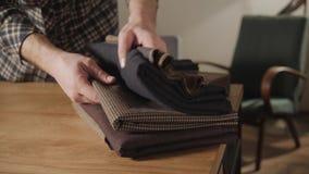 Επιλέγει το μαλλί από το σωρό Νεαρός άνδρας που εργάζεται ως ράφτης και που χρησιμοποιεί μια ράβοντας μηχανή στο εργαστήριο φιλμ μικρού μήκους
