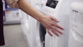 Επιλογή του mashine πλύσης στο κατάστημα συσκευών Προφθάνοντας χέρι τη σειρά απόθεμα βίντεο