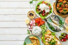 Επιλογή των παραδοσιακών ελληνικών τροφίμων - σαλάτα, meze, πίτα, ψάρια, tzatziki, dolma στο ξύλινο υπόβαθρο στοκ φωτογραφία