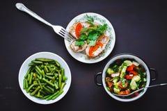 Επιλογή των υγιών τροφίμων Φασόλια σειράς, ντομάτα και σαλάτα αγγουριών, ψημένα ψάρια στα πιάτα στοκ φωτογραφία με δικαίωμα ελεύθερης χρήσης