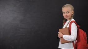 Επιμελής μαθήτρια με το σακίδιο και βιβλίο που δείχνει το δάχτυλο στον πίνακα, μάθημα απόθεμα βίντεο