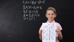 Επιμελής χαμογελώντας μαθητής που παρουσιάζει άριστη δοκιμή, math άσκηση γραπτή πίσω απόθεμα βίντεο