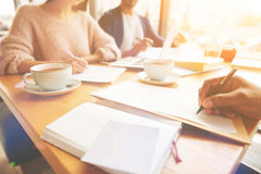 Επιμελείς σπουδαστές που μελετούν μαζί στην καφετέρια Στοκ Εικόνες
