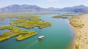 Επιπλέοντα σώματα βαρκών μηχανών στον ποταμό, δίπλα στην αμμώδη ακτή Ποταμός Dalyan και οβελός Iztuzu r απόθεμα βίντεο