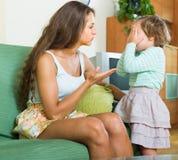 Επιπλήττοντας παιδί γυναικών στο σπίτι Στοκ Εικόνες