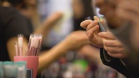 Επισκέπτες έκθεσης ομορφιάς που επιλέγουν τα προϊόντα σύνθεσης, αγοραστές που ψωνίζουν στη λεωφόρο φιλμ μικρού μήκους