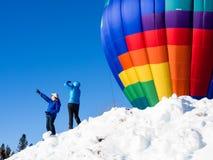 Επισκέπτες που απολαμβάνουν τη θέα των μπαλονιών ζεστού αέρα που διογκώνουν και που απογειώνονται Στοκ φωτογραφία με δικαίωμα ελεύθερης χρήσης