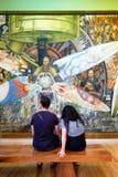 Επισκέπτες που θαυμάζουν τις τοιχογραφίες από το Diego Rivera Palacio de Bellas Artes στην Πόλη του Μεξικού Στοκ Φωτογραφίες