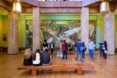 Επισκέπτες που θαυμάζουν τις τοιχογραφίες από το Diego Rivera Palacio de Bellas Artes στην Πόλη του Μεξικού Στοκ Εικόνες