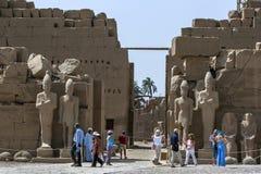 Επισκέπτες στο ναό Karnak (ναός Amun) σε Luxor στον περίπατο της Αιγύπτου κοντά σε μια σειρά αρχαίων αγαλμάτων στοκ φωτογραφίες