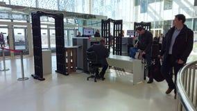 Επισκέπτες της επιστημονικής διάσκεψης που περνούν το έλεγχο ασφαλείας φιλμ μικρού μήκους