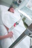 Επισκέπτης που κρατά το χέρι ενός ασθενή στο ICU Στοκ Εικόνες
