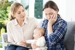 Επισκέπτης υγείας με τη νέα μητέρα που υποφέρει με την κατάθλιψη Στοκ Εικόνα