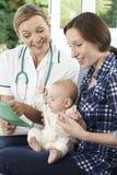 Επισκέπτης υγείας που συζητά το φυλλάδιο με το μωρό εκμετάλλευσης μητέρων σε Ho Στοκ φωτογραφίες με δικαίωμα ελεύθερης χρήσης