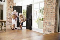 Επισκεπτόμενοι παππούδες και γιαγιάδες που αγκαλιάζουν τα εγγόνια καθώς φθάνουν στοκ εικόνες
