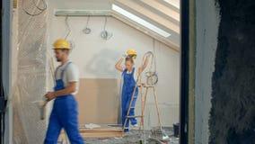 Επισκευές οικοδόμων κατασκευής makin στο διαμέρισμα Οι κύριοι εργάζονται με το τρυπάνι και την ηλεκτρική ενέργεια χρωμάτων φιλμ μικρού μήκους