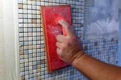 Επισκευές στο διαμέρισμα: εγκατάσταση του κεραμιδιού μωσαϊκών στον τοίχο Στοκ Εικόνα