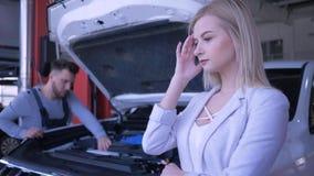 Επισκευή αυτοκινήτων, δυστυχισμένο θηλυκό πελατών που ανατρέπεται για το σπασμένο αυτοκίνητο με την ανοικτή κουκούλα που επισκευά απόθεμα βίντεο