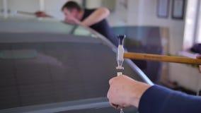 Επισκευή ζουλιγμάτων Paintless Ο αρσενικός κύριος με ένα σφυρί επιδιορθώνει προσεκτικά τα αυτοκίνητα στο εργαστήριο Δύο άτομα που φιλμ μικρού μήκους
