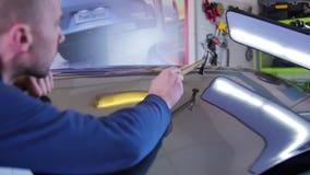 Επισκευή ζουλιγμάτων Paintless Ο αρσενικός κύριος με ένα σφυρί επιδιορθώνει προσεκτικά τα αυτοκίνητα στο εργαστήριο Αυτοκίνητο, ε απόθεμα βίντεο