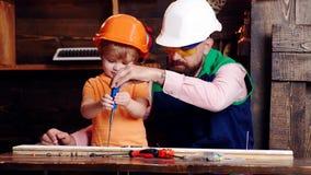 Επισκευή και έννοια εργαστηρίων Πατέρας, γονέας με τη γενειάδα που διδάσκει λίγο γιο για να χρησιμοποιήσει το κατσαβίδι εργαλείων απόθεμα βίντεο
