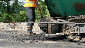 Επισκευή μιας εθνικής οδού, εργασίες οδοποιίας ο εργαζόμενος σε ένα πορτοκαλί γιλέκο, ειδικός ένας ομοιόμορφος, με ένα φτυάρι ξεφ απόθεμα βίντεο