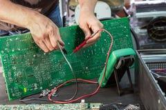 Επισκευή μιας μονάδας παροχής ηλεκτρικού ρεύματος στο κέντρο υπηρεσιών, διάγνωση ελαττωμάτων από τις μετρώντας συσκευές στοκ εικόνα με δικαίωμα ελεύθερης χρήσης