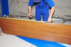 Επισκευή πορτών γκαράζ Ανάδοχος που μετρά τον πίνακα πορτών γκαράζ με την ταινία μέτρου στοκ φωτογραφία με δικαίωμα ελεύθερης χρήσης