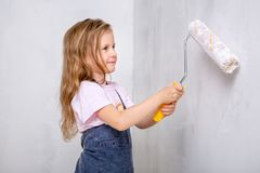 Επισκευή στο διαμέρισμα Η ευτυχής οικογενειακή μητέρα και λίγη κόρη στις μπλε ποδιές χρωματίζουν τον τοίχο με το άσπρο χρώμα Πόνο στοκ φωτογραφία με δικαίωμα ελεύθερης χρήσης
