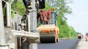Επισκευή της εθνικής οδού, εργασίες οδοποιίας στο πρώτο πλάνο, στη μηχανή για την άσφαλτο, ο εργαζόμενος άφησε το ειδικό πορτοκάλ απόθεμα βίντεο