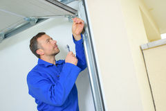 Επισκευή της ελαττωματικής πόρτας γκαράζ στοκ εικόνα