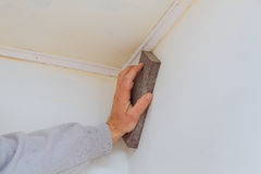 Επισκευή δωματίων, χέρι που στρώνει με άμμο τον τοίχο με ένα στρώνοντας με άμμο σφουγγάρι Στοκ Εικόνα